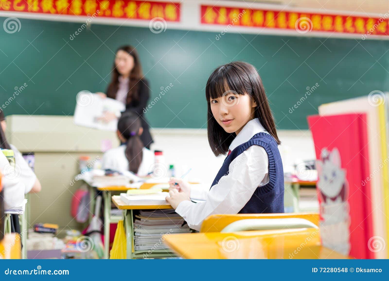 Download Азиатский студент девушки в школьной форме уча в классе Стоковое Фото - изображение насчитывающей рука, мило: 72280548