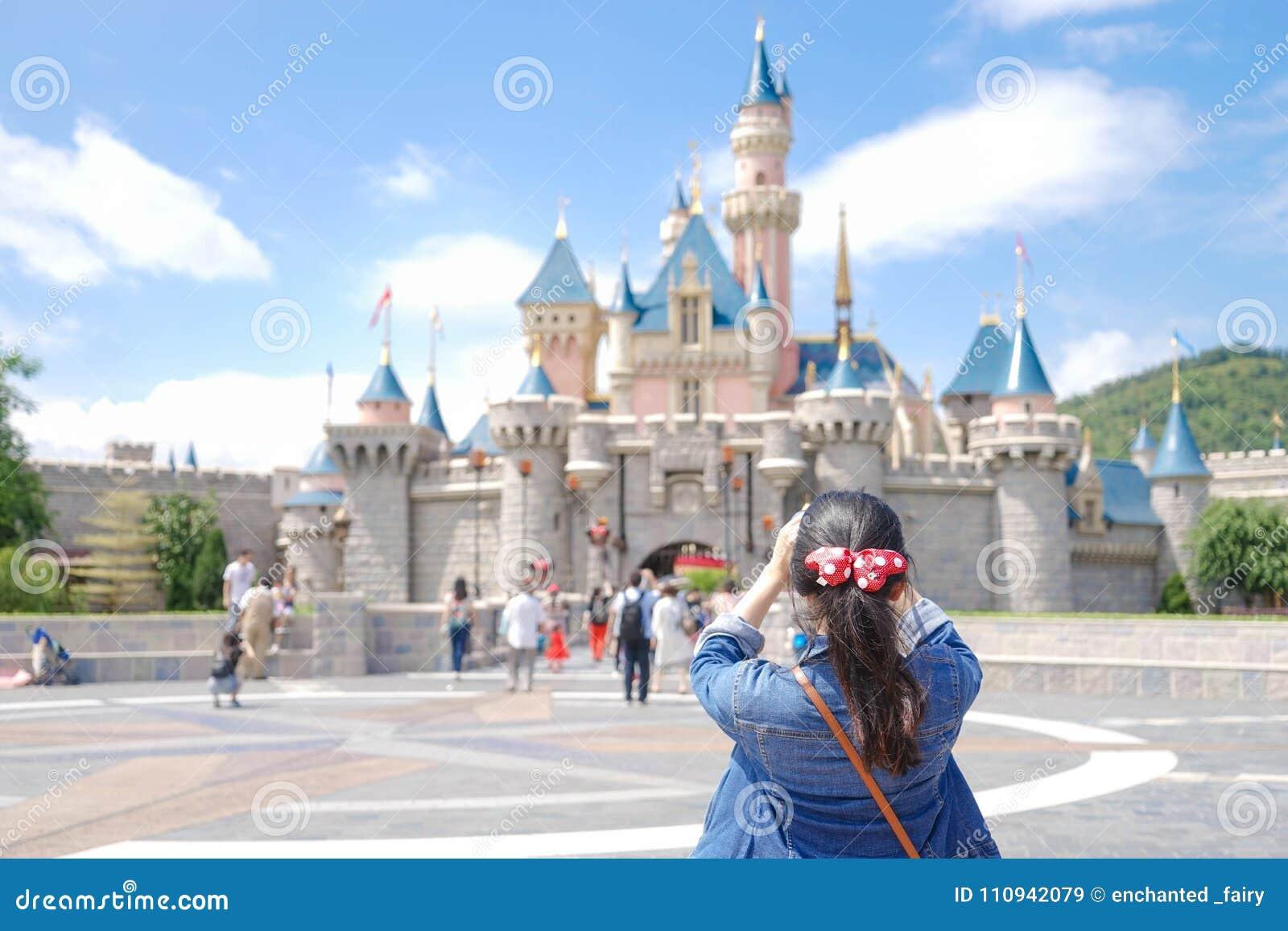 Азиатский турист принимает фото перед замком Диснейленда в Гонконге