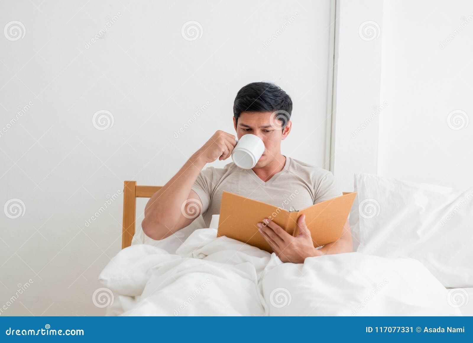 Азиатский человек выпивая чашку кофе или завтрак в кровати