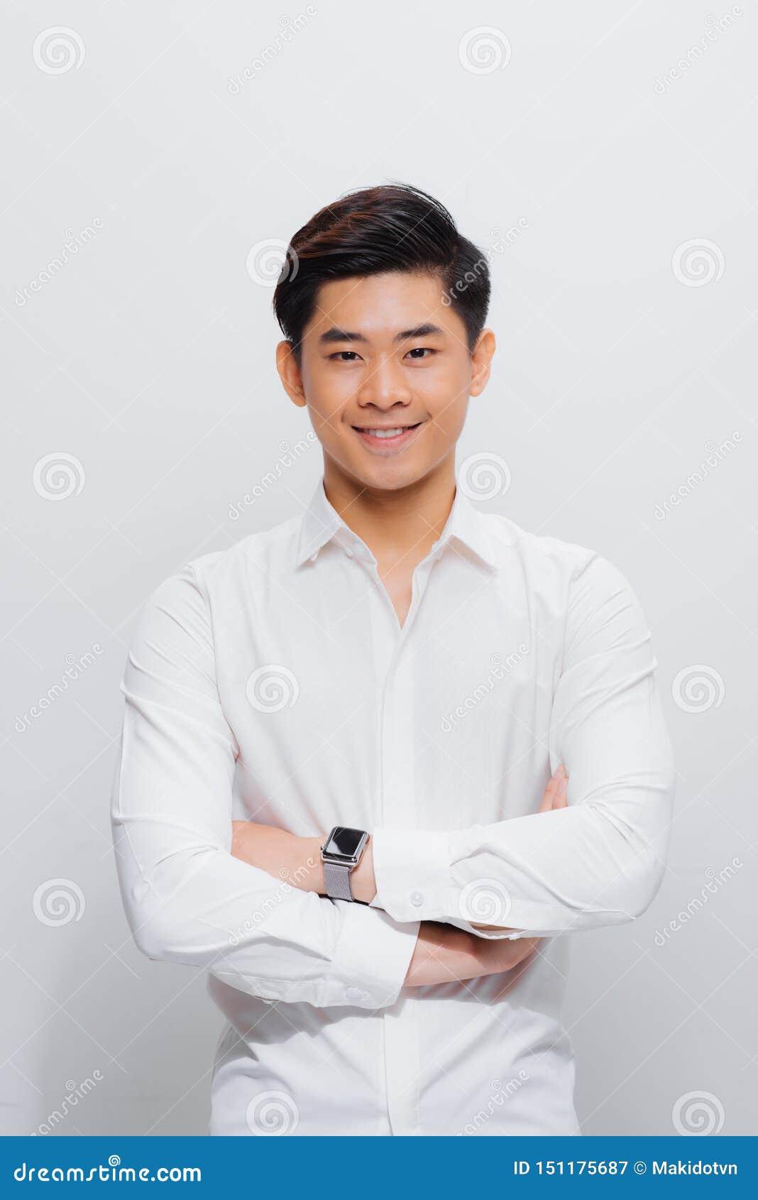 Азиатский человек в рубашке, смотря на камере, со сложенными руками