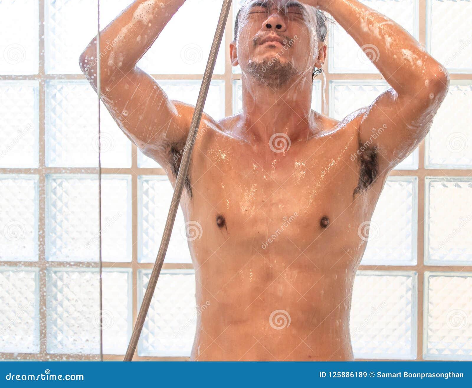 Азиатский человек принимая ливень в ванной комнате