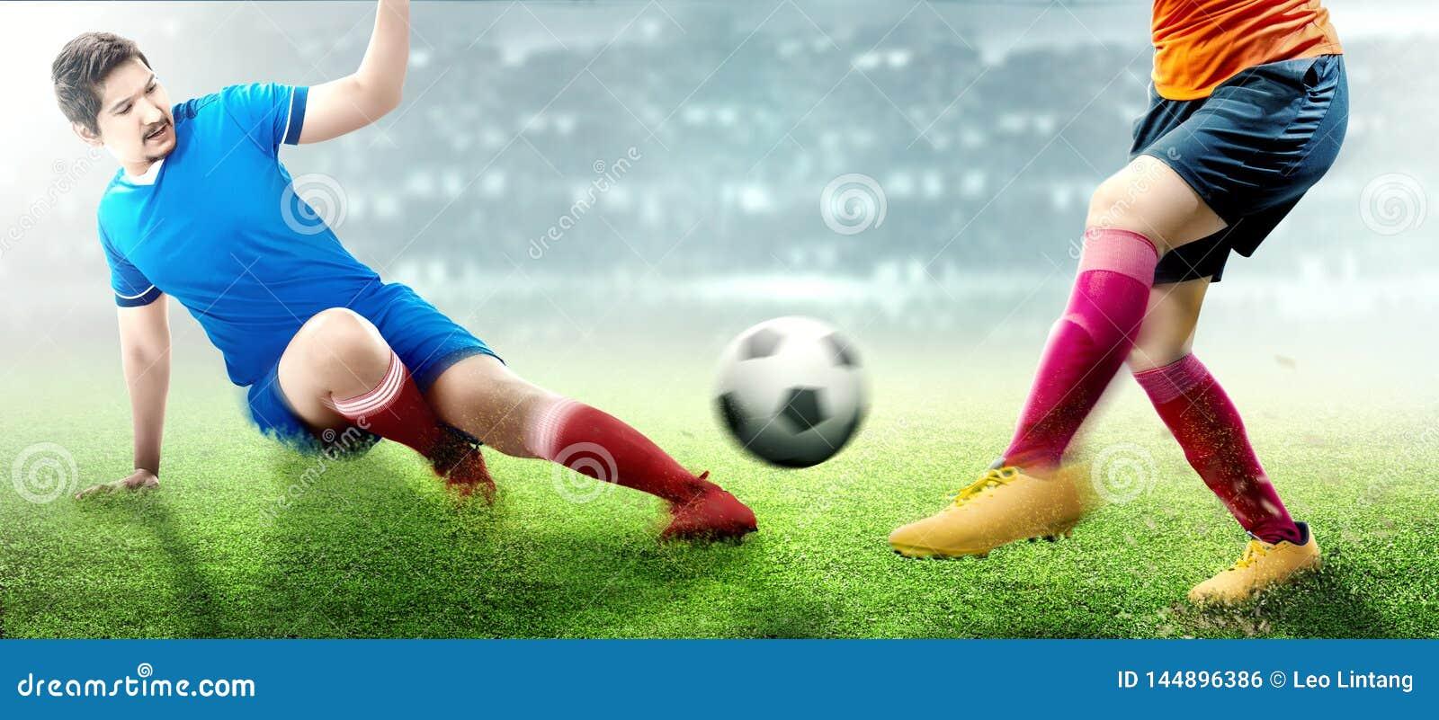 Азиатский человек футболиста в голубом jersey сползая для решения шарика