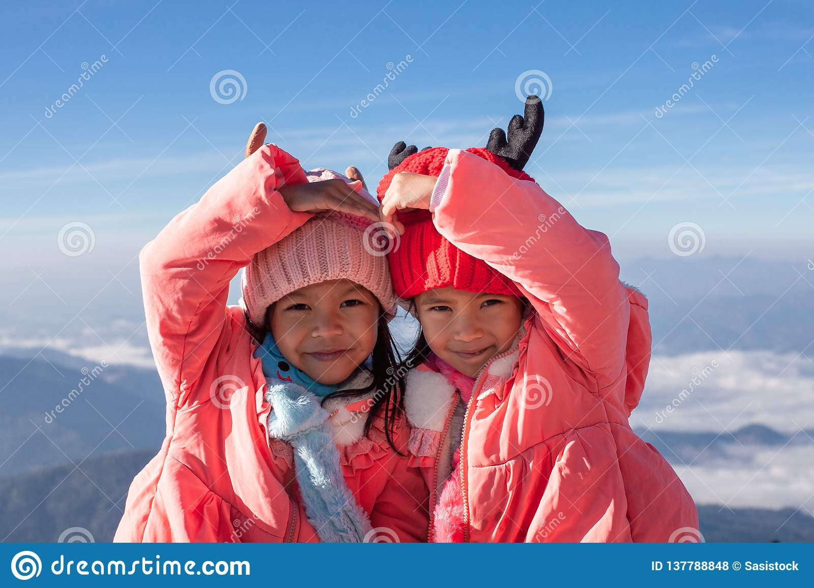 2 азиатских девушки ребенка нося свитер и теплую шляпу делая сердце вместе с любовью на красивых тумане и горе