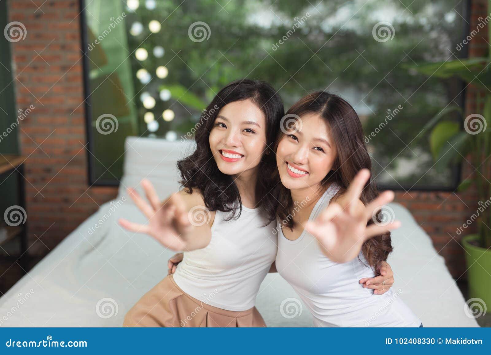 2 азиатских женщины в спальне на кровати имеют потеху