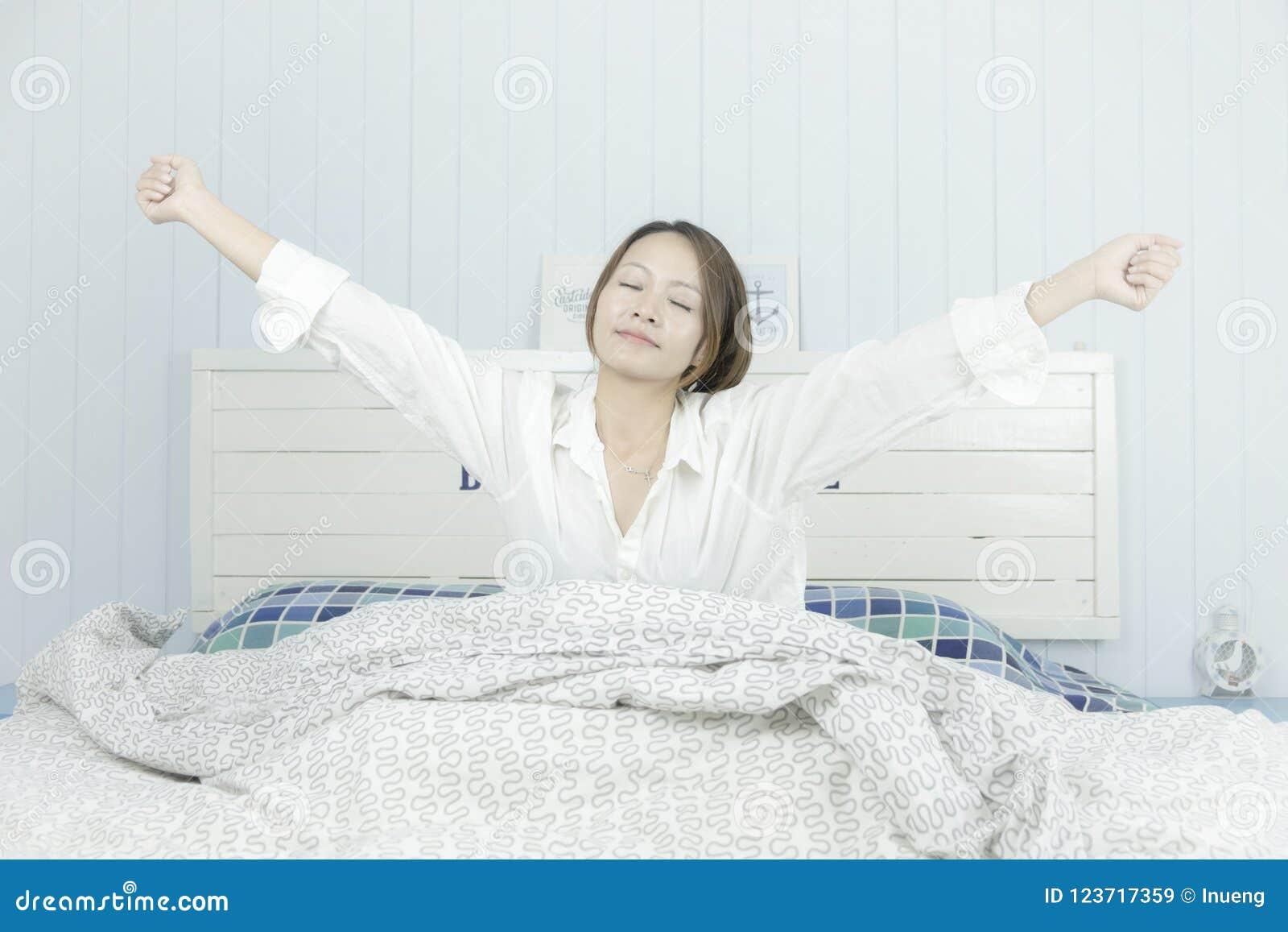 азиатское красивейшее слушая нот к женщине Слушая концепция наушников музыки Привлекательная азиатская женщина просыпаясь на кров