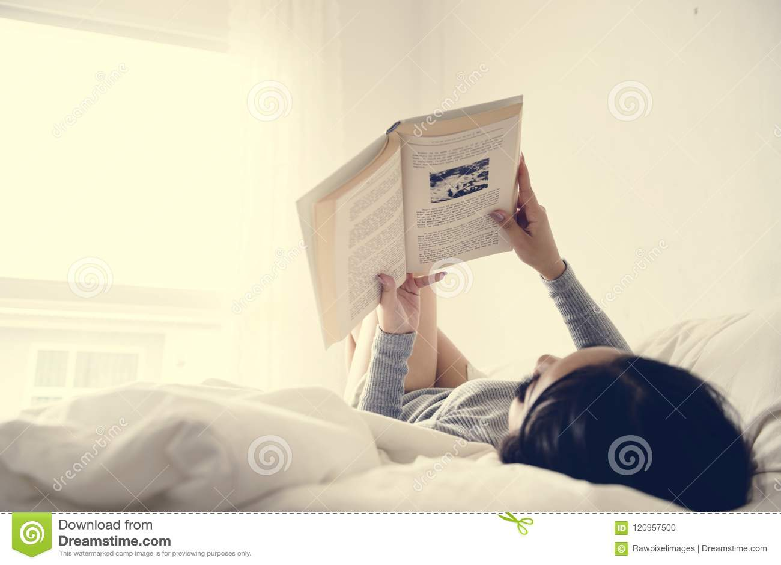 Азиатское чтение женщины на кровати в яркой минимальной комнате