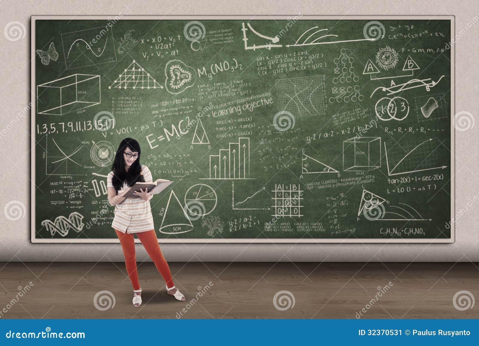 Азиатское чтение студентки на написанной доске в классе