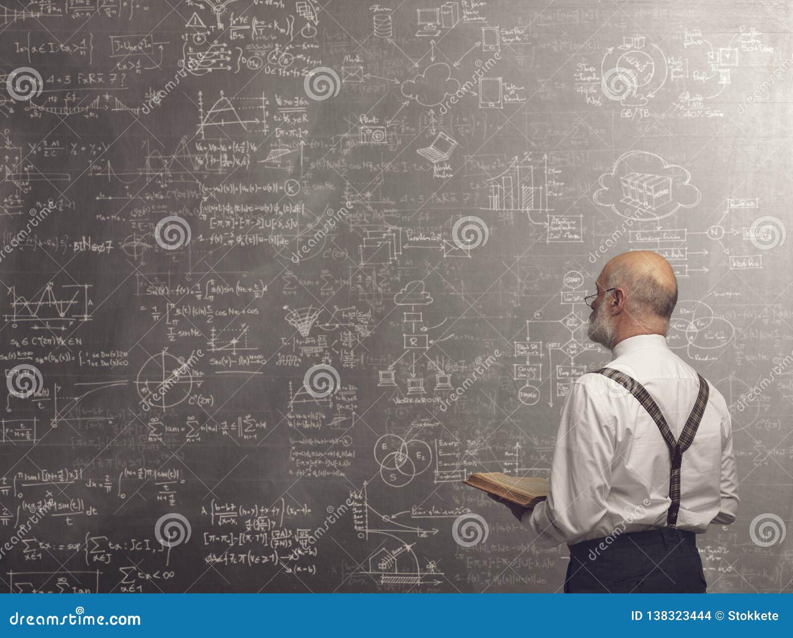 Академичный профессор уча и держа книге