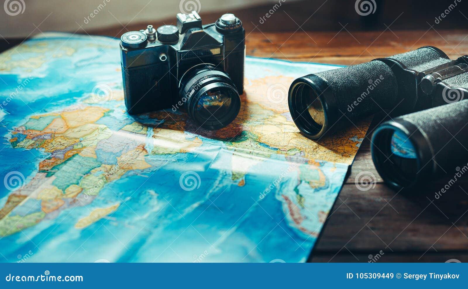Аксессуары для камеры, карты и биноклей фильма перемещения винтажной на деревянном столе, вид спереди Путешествие Concep разведчи