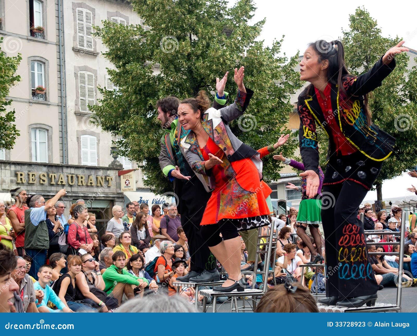 Актеры садить на насест на табуретках в улице.