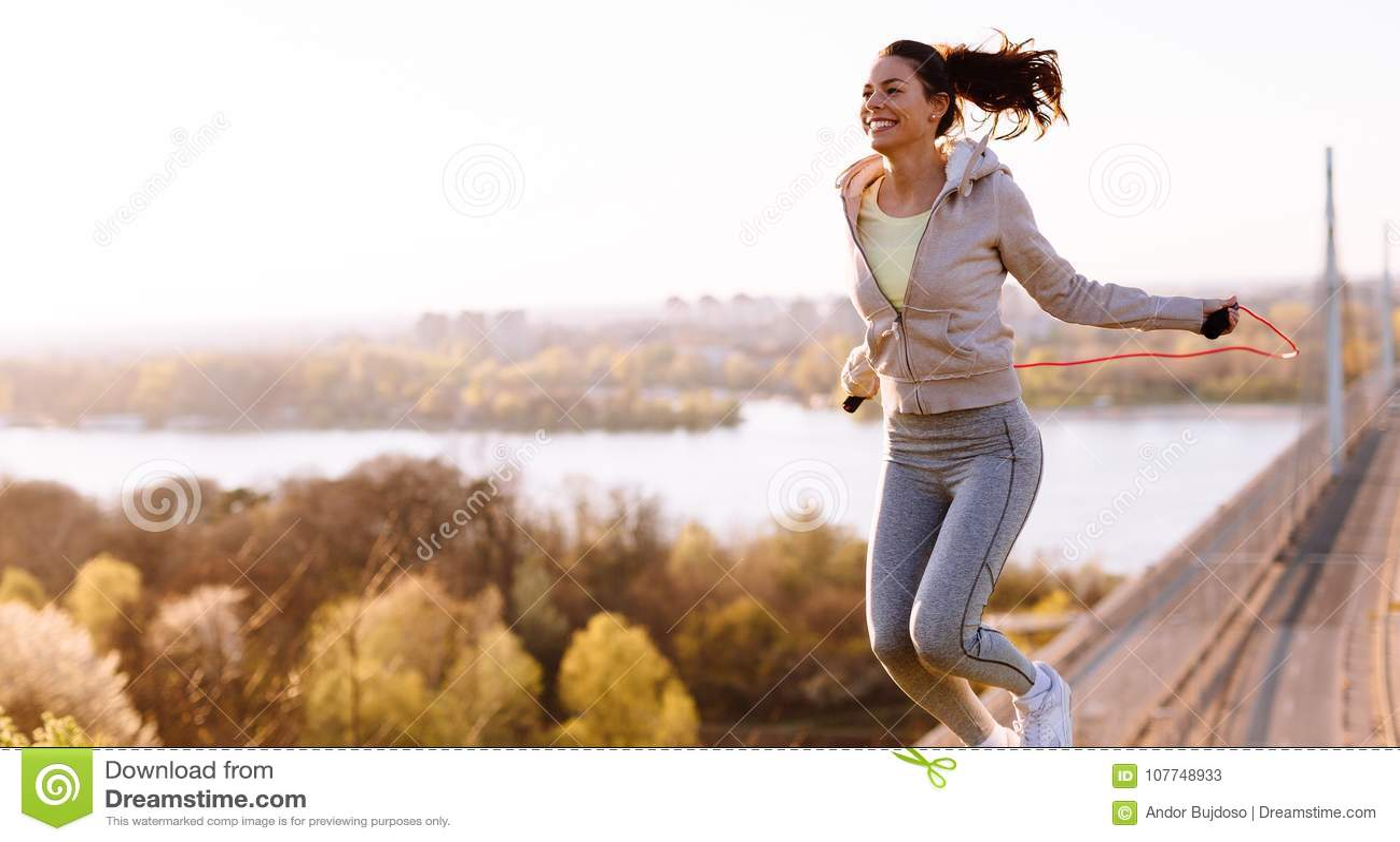 Активная женщина скача с прыгая веревочкой outdoors