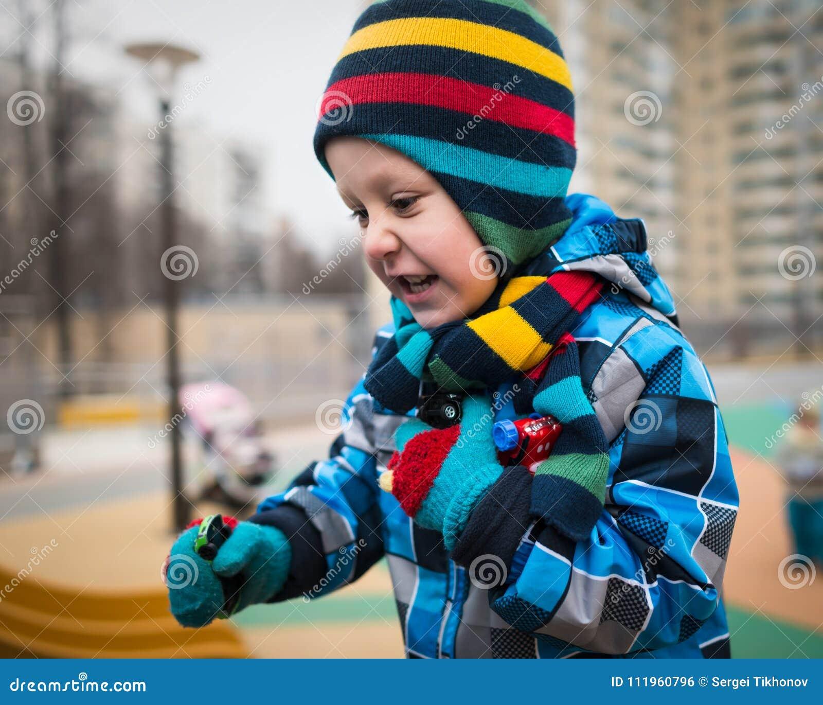 Активный мальчик бежит вокруг на спортивной площадке и имеет потеху
