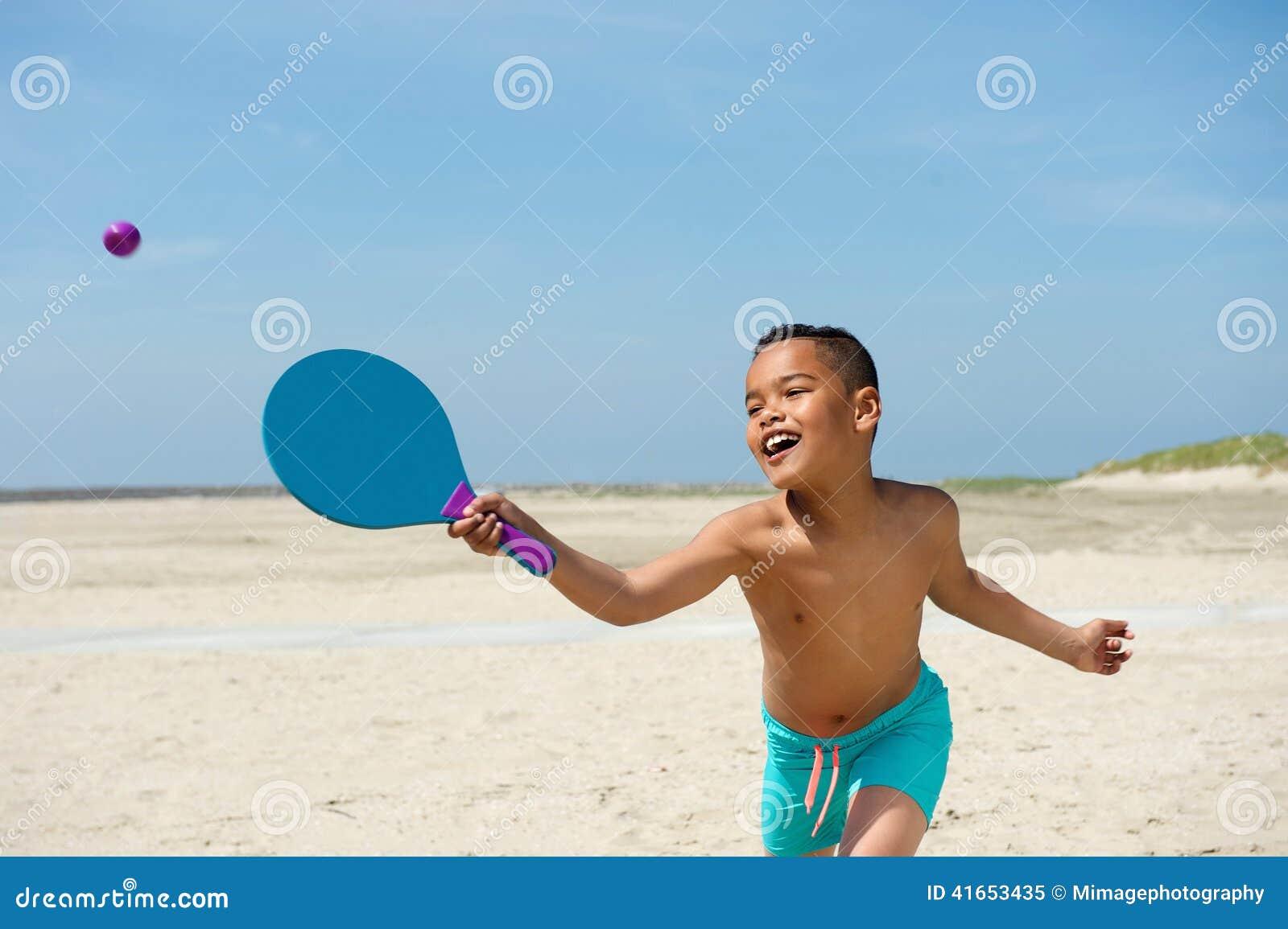 Активный мальчик играя на пляже