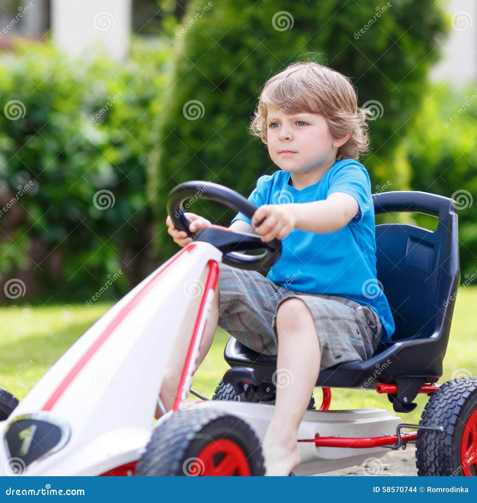 Активный мальчик имея потеху и управляя гоночной машиной игрушки