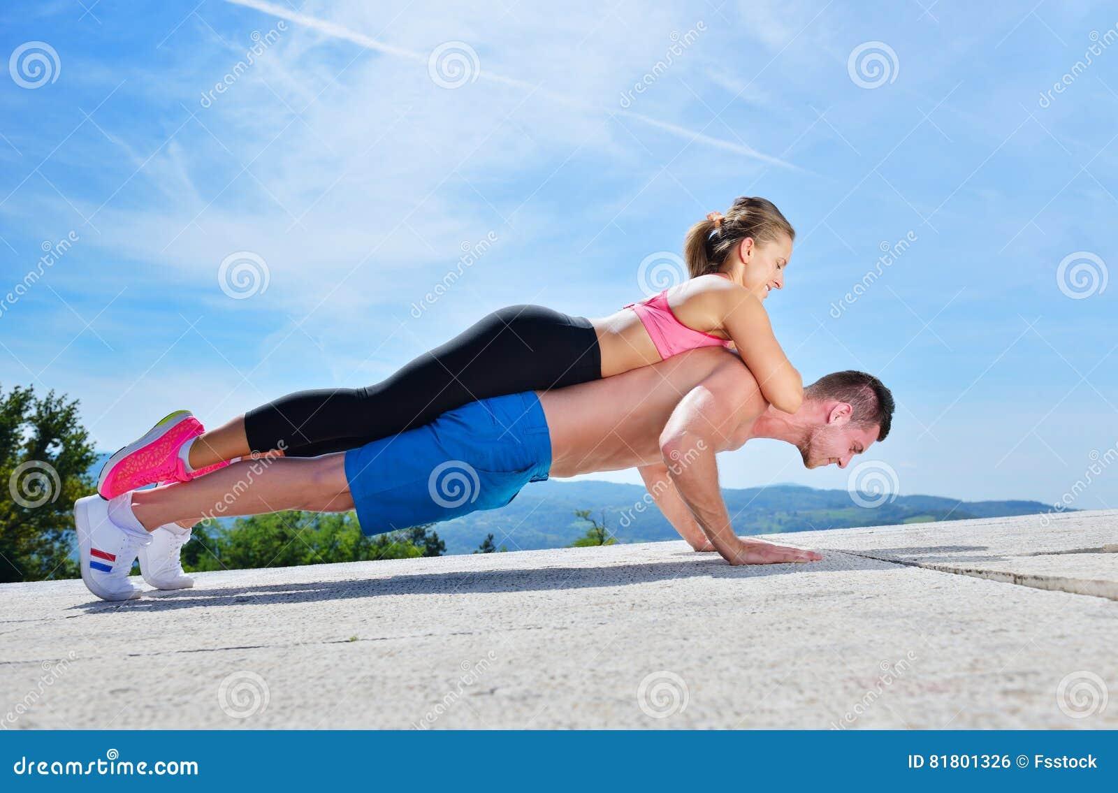 Активный молодой человек и женщина работая делать нажимают поднимают