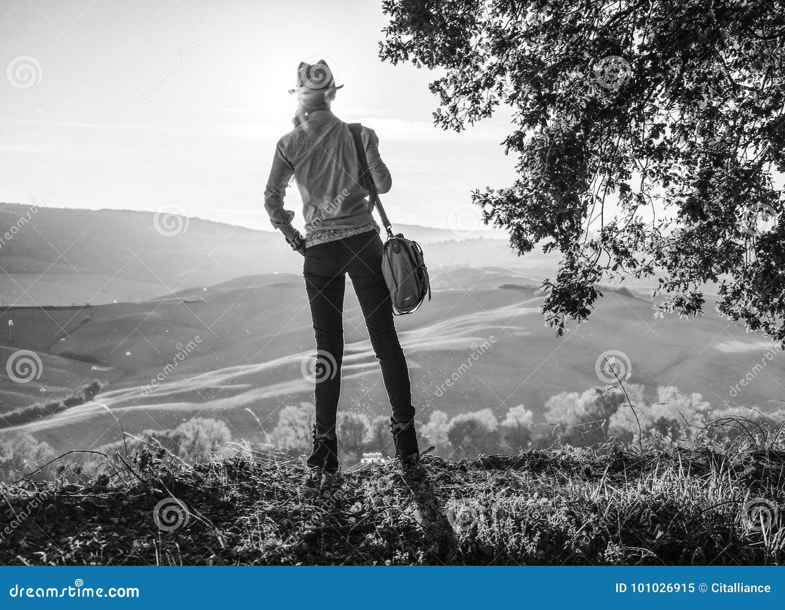 Активный hiker женщины в шляпе с сумкой наслаждаясь заходом солнца в Тоскане