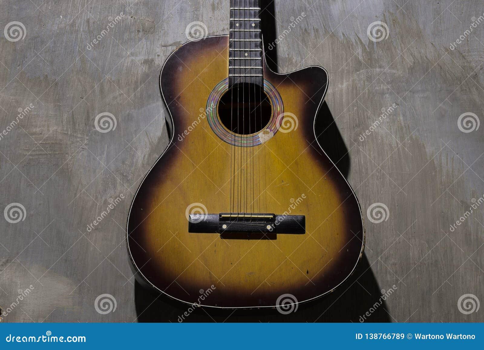 Акустическая гитара на предпосылке стены