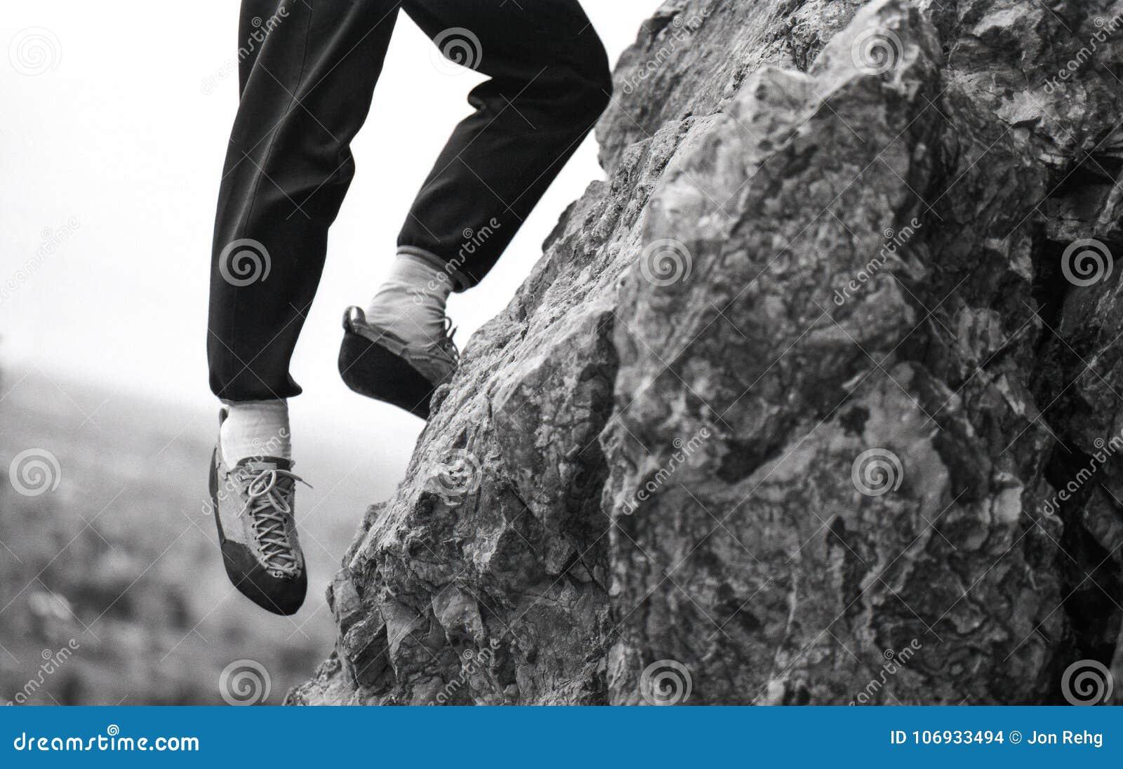 Альпинист утеса при одна нога вися с края выхода на поверхность скалы над смотреть долину ниже