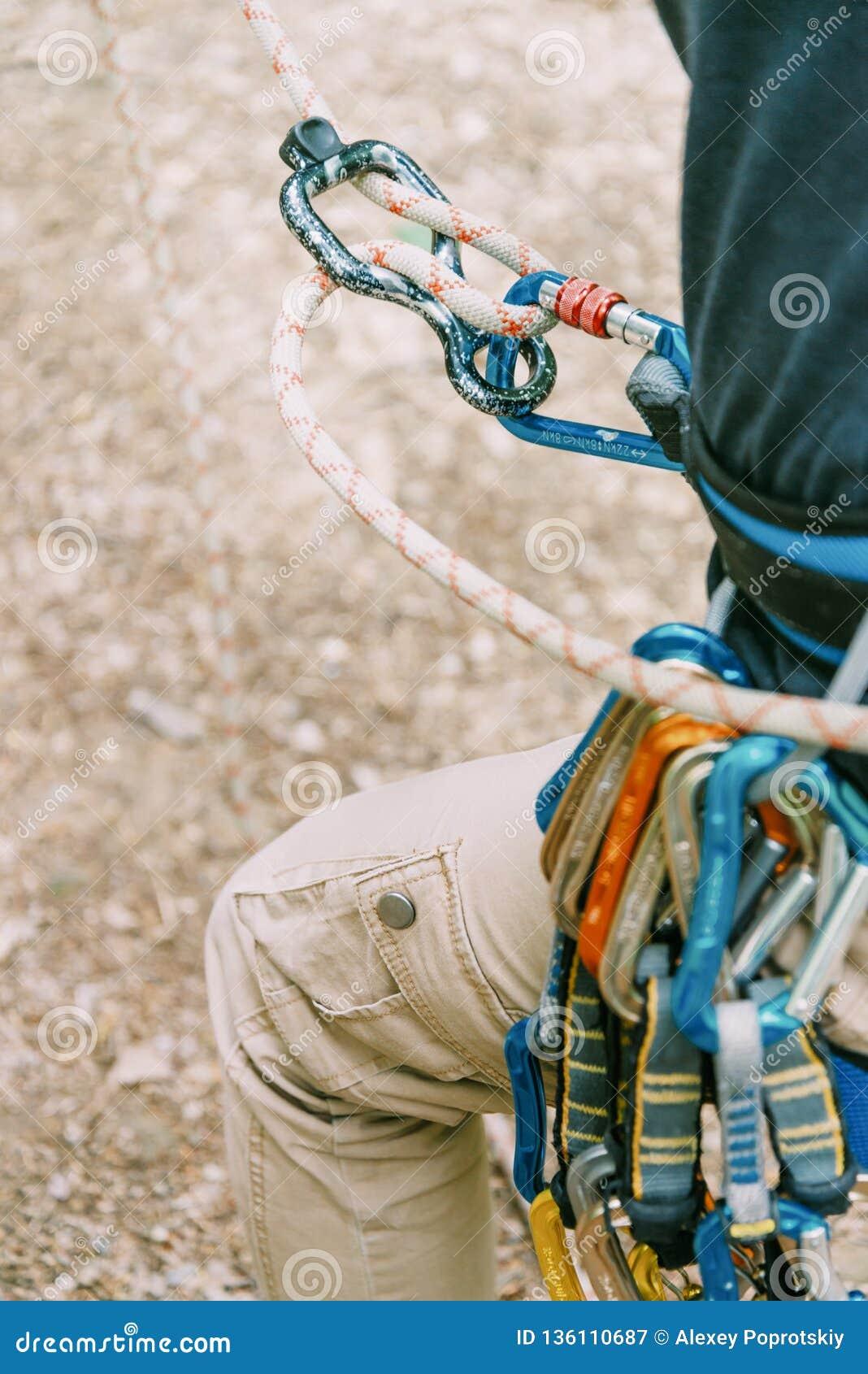 Альпинист belaying с системой безопасности веревочки