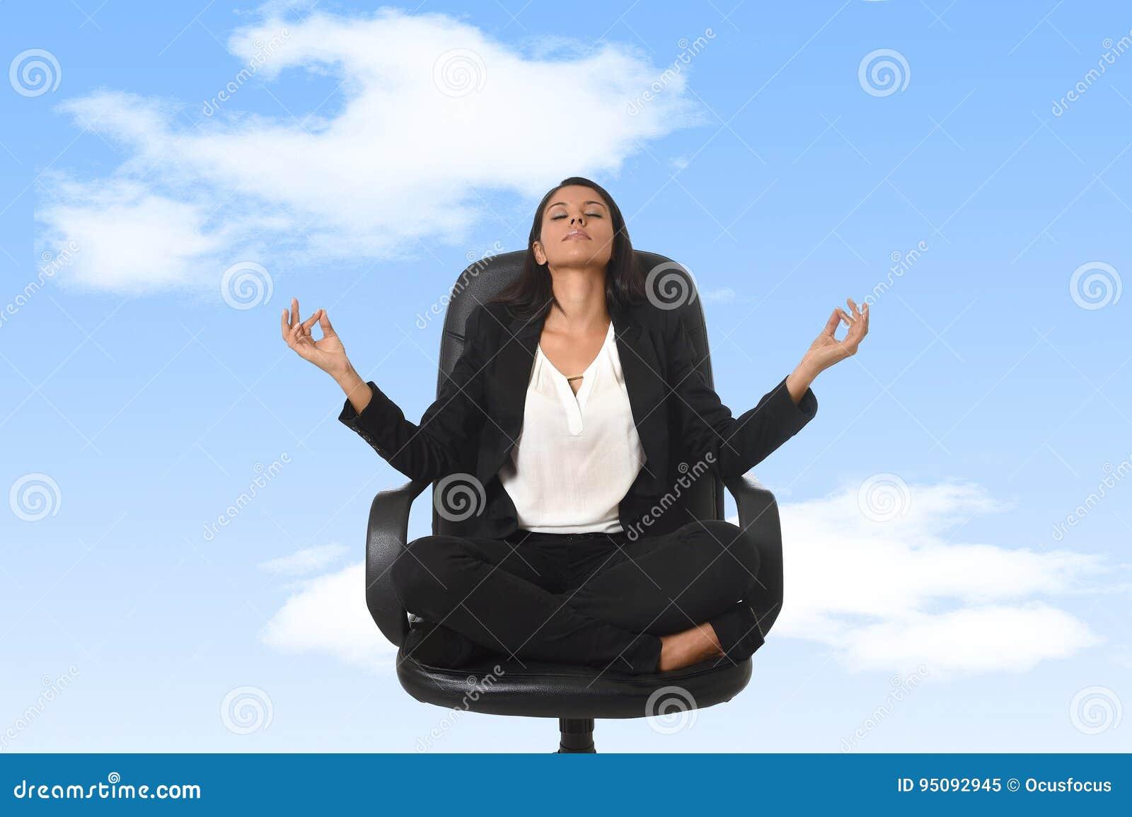 Американская бизнес-леди сидя на стуле офиса в йоге и раздумье позиции лотоса практикуя