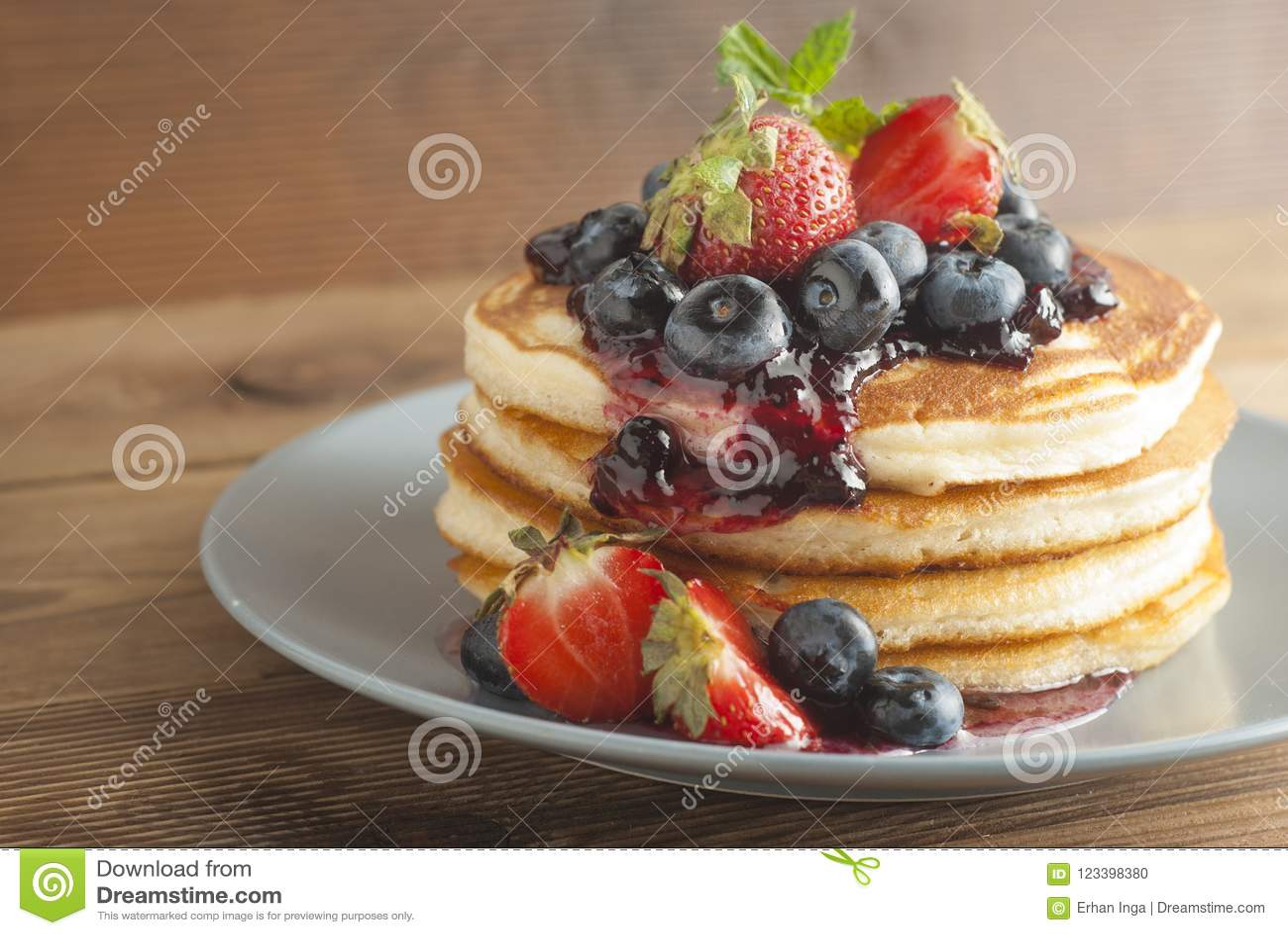 Американские блинчики или оладь оладьи служили с вареньем клубники и голубики, очень вкусным десертом для завтрака, деревенского
