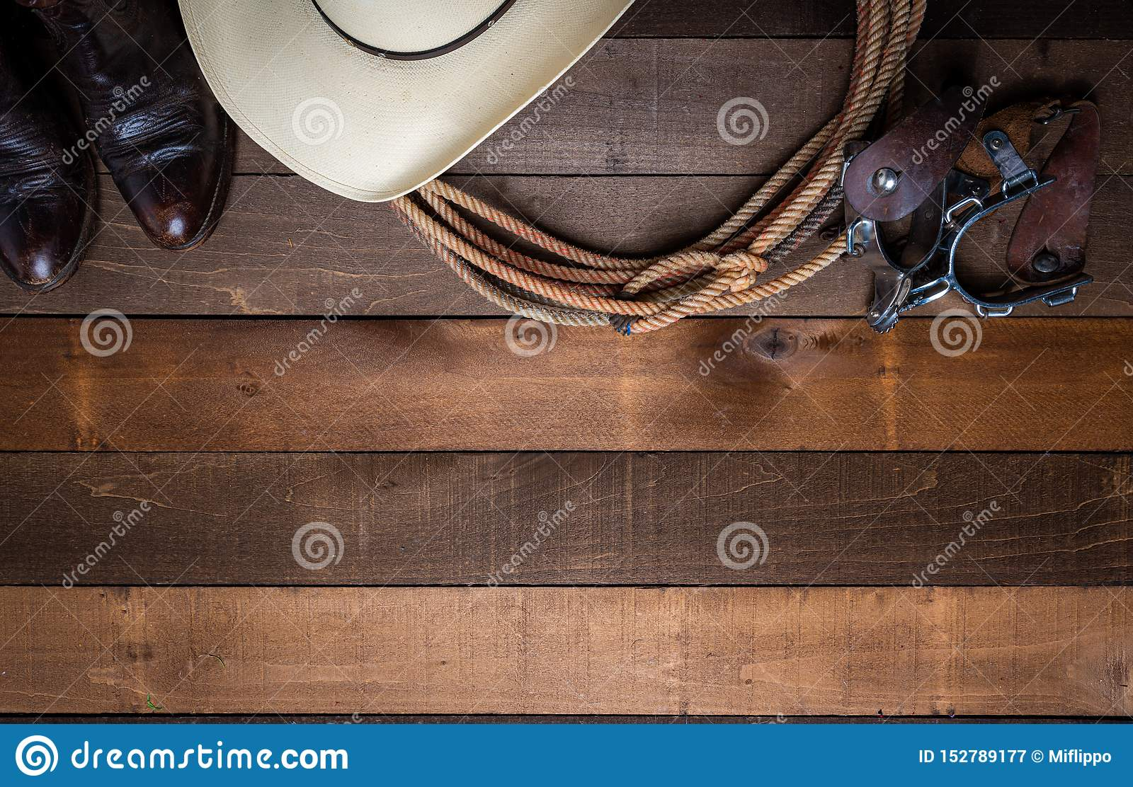 Американские детали ковбоя incluing шпоры лассо и традиционная соломенная шляпа на деревянной предпосылке планки