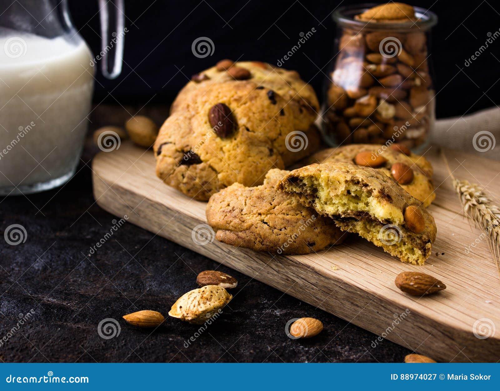 Американские печенья shortbread с падениями шоколада и кувшин молока и миндалин Темная предпосылка grunge Мистический свет
