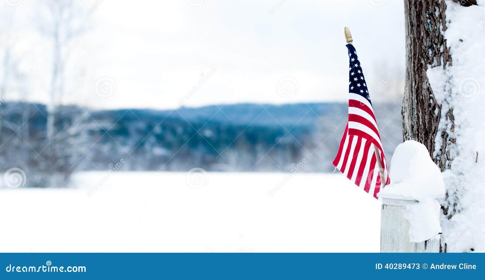 Американский флаг на столбе загородки перед снежным полем