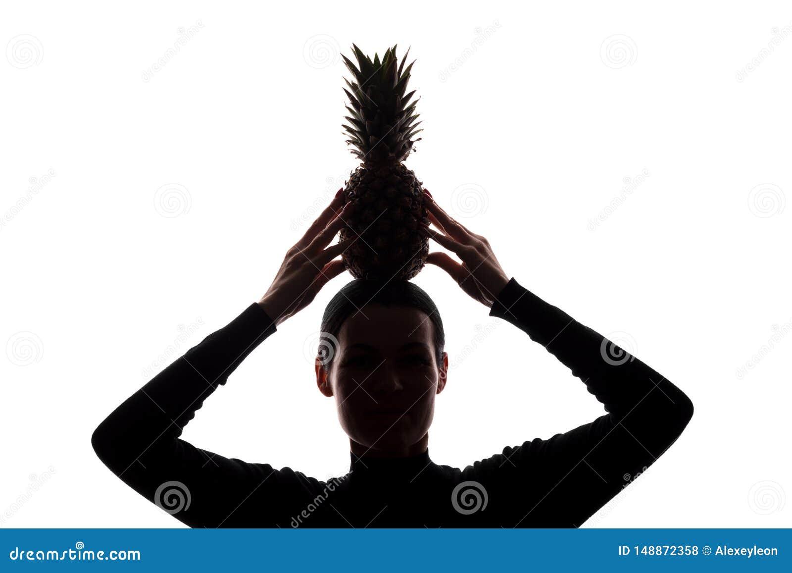 Ананас в руках женщины над головой - силуэтом