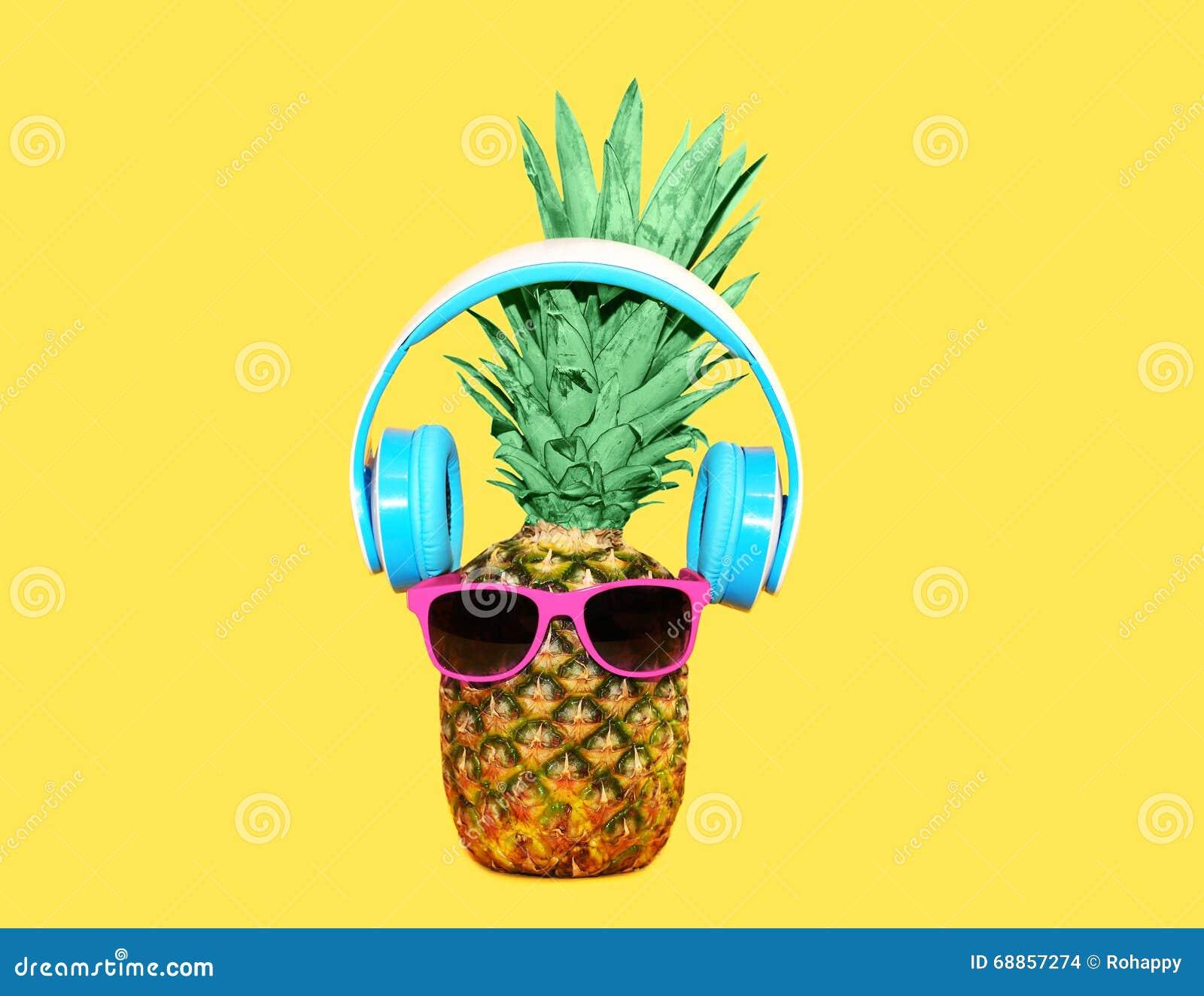 Ананас моды с солнечными очками и наушниками слушает музыка над желтой предпосылкой, концепцией ананаса