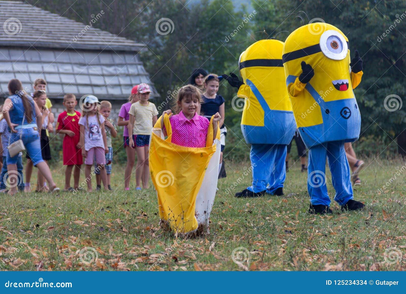 Аниматор в костюме миньона играя с детьми на праздник деревни Kamennomostskiy в равенстве осени