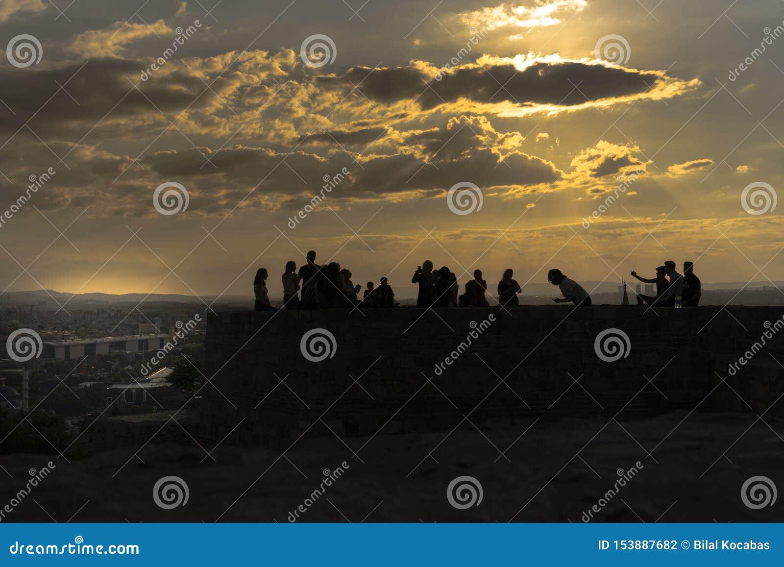 Анкара/Турция - 6-ое июля 2019: Замок Анкара в заходе солнца и людях наслаждаясь на верхней части замка