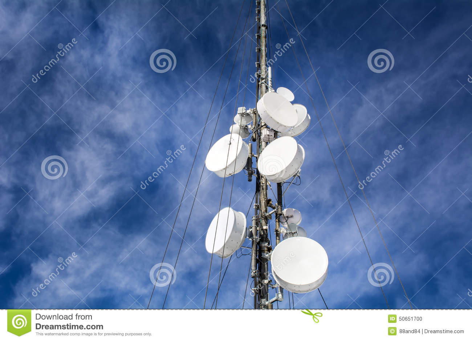 Антенны на передвижной сети возвышаются на голубом небе Глобальная система для мобильных телефонных связей
