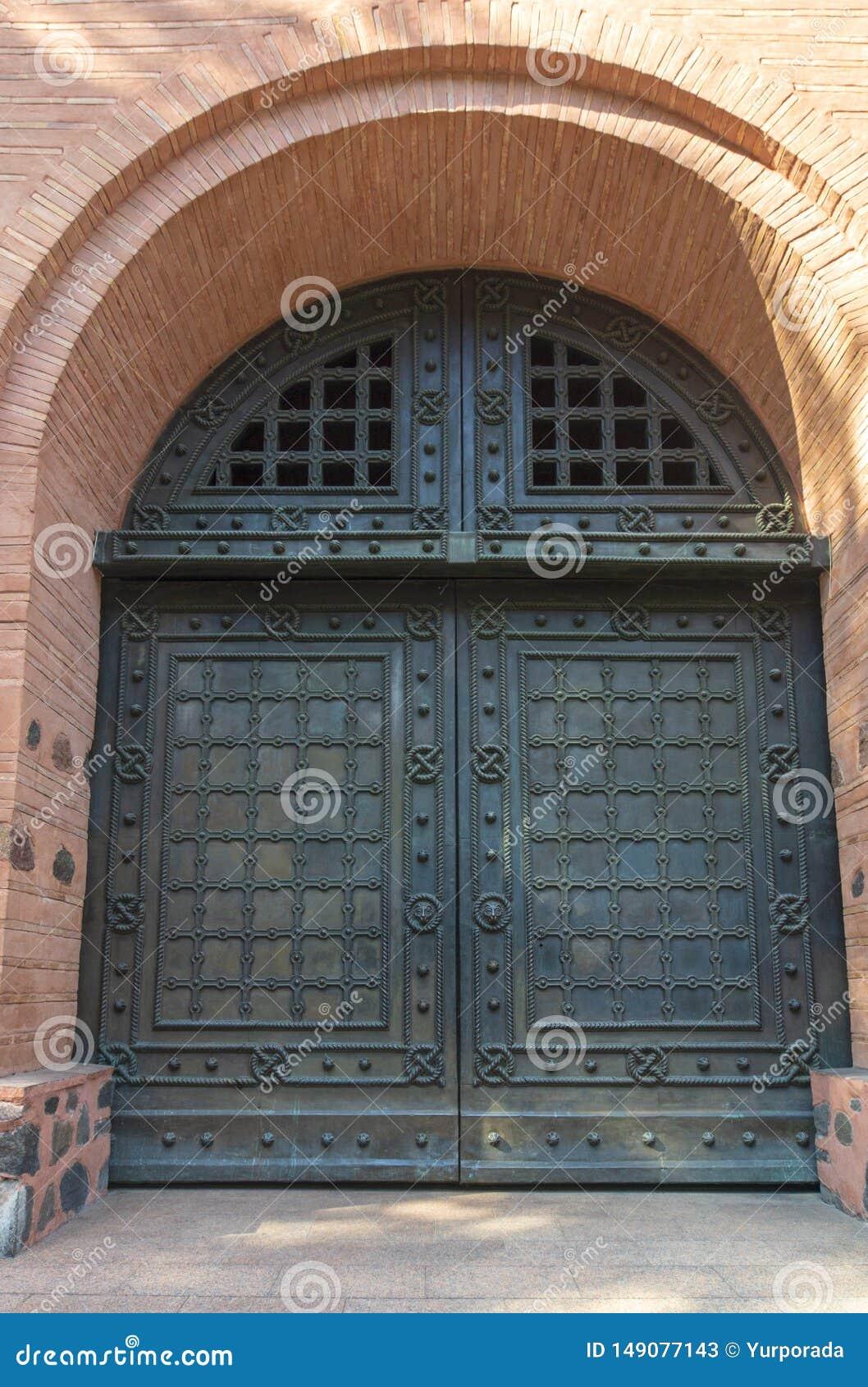 Античная деревянная дверь с металлическими пластинами и ручками