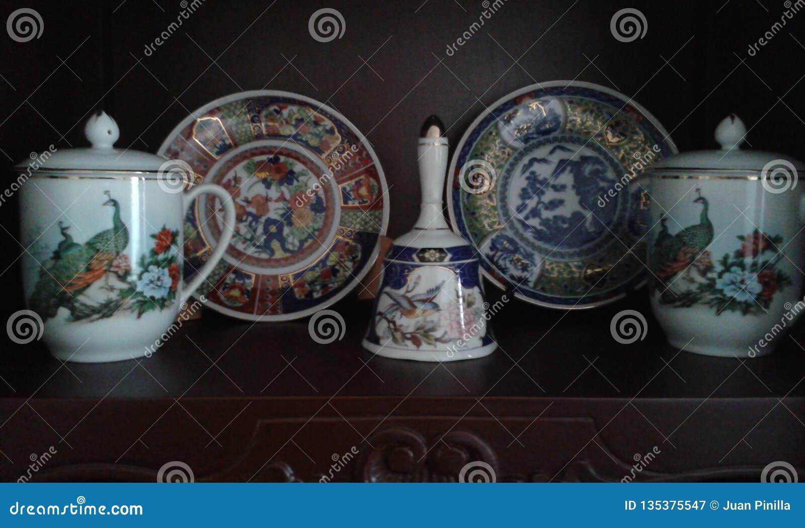 Античные блюда керамики над деревянной мебелью