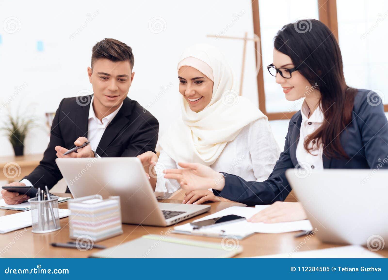 Арабская женщина в hijab работает в офисе вместе с ее коллегами