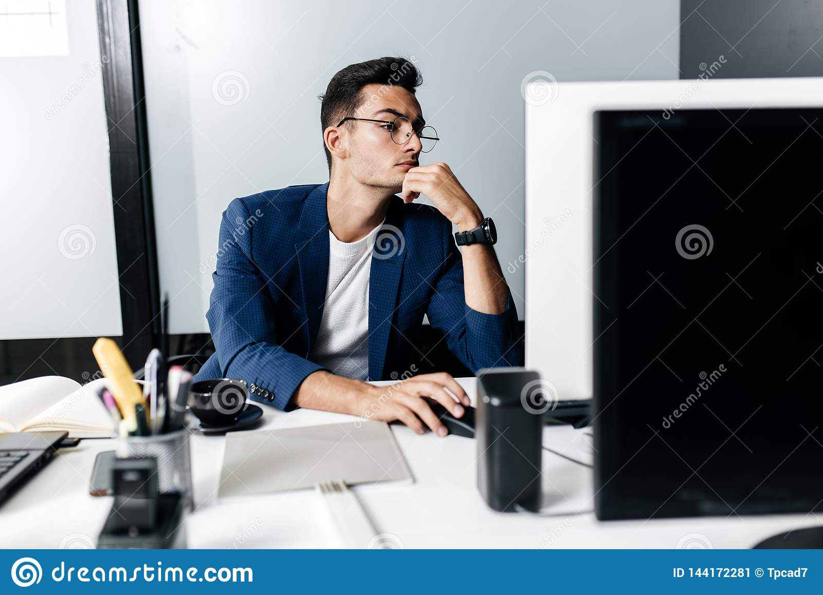 Архитектор молодого человека в стеклах одетых в деловом костюме сидит на столе перед компьютером в офисе