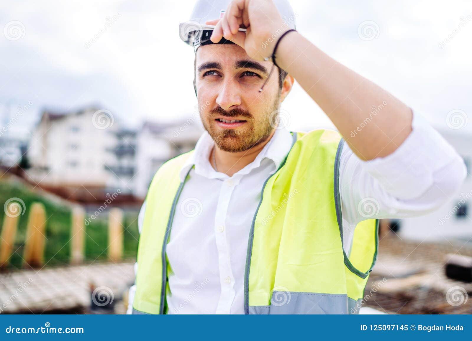 архитектор работая на шляпе строительной площадки, носить трудной и жилете безопасности