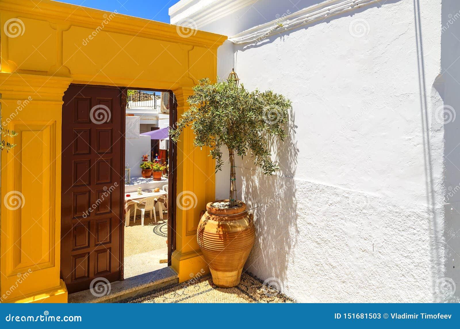 Архитектура древнегреческого с традиционными дверями и декоративной мостовой в городке Lindos, острове Родоса, Греции, Европе