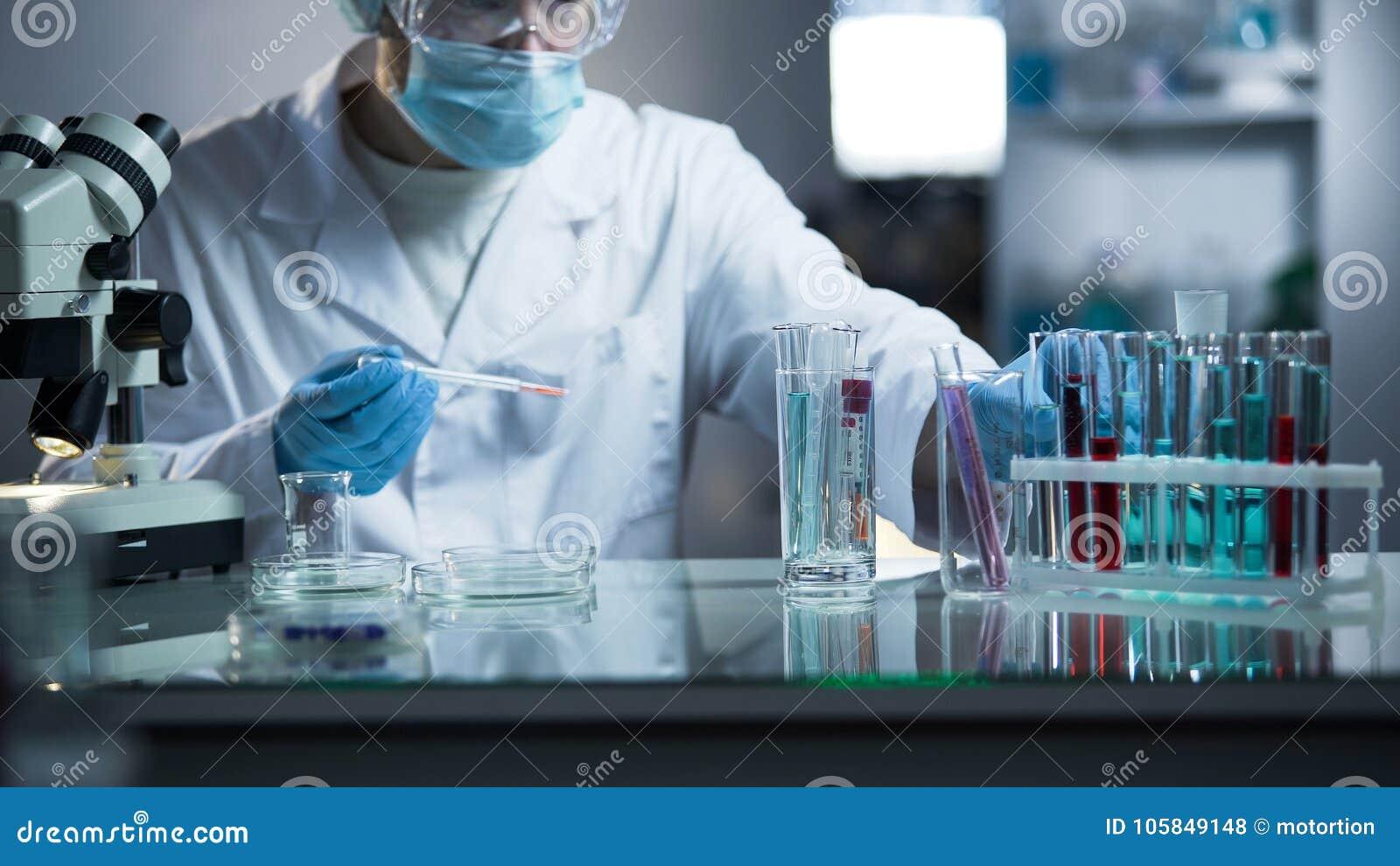 Ассистент медицинской лаборатории принимая генетический материал для рассмотрения на отцовстве