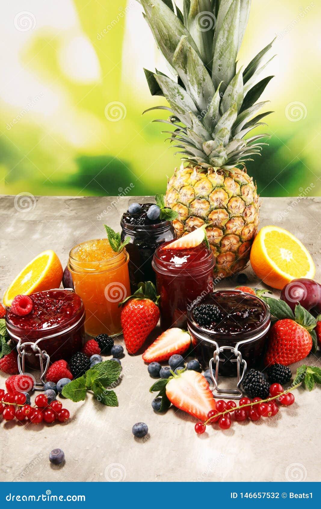 Ассортимент варениь, сезонных ягод, слив, мяты и плодов в стеклянном опарнике