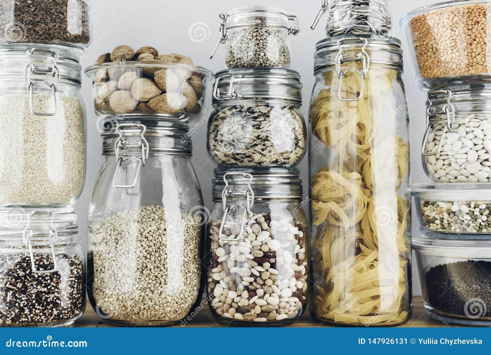 Ассортимент сырых зерен, хлопьев и макаронных изделий в стеклянных опарниках на деревянном столе r