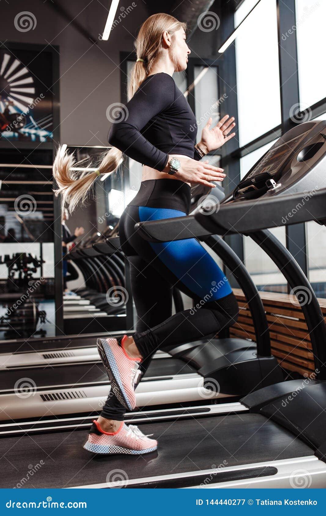Атлетическая девушка с длинными светлыми волосами одетыми в sportswear бежит на третбане перед окнами внутри