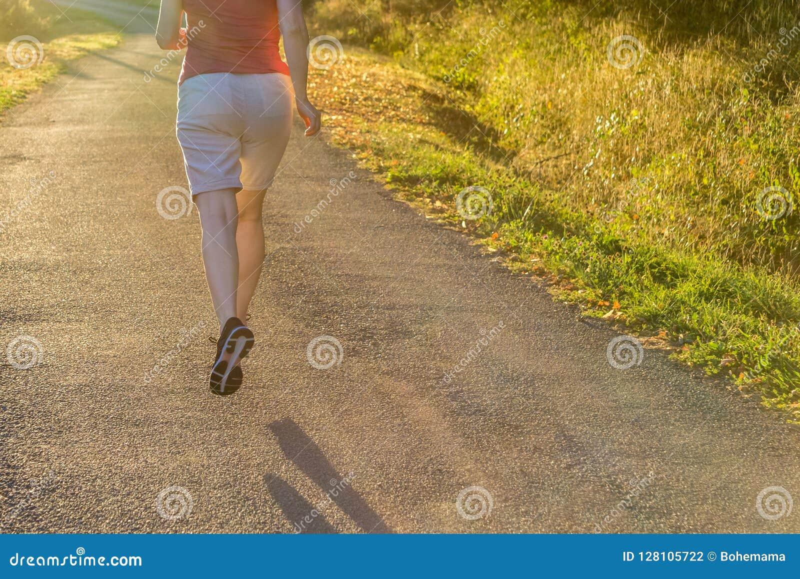 Атлетическая женщина бежать на следе сельской местности в свете восхода солнца