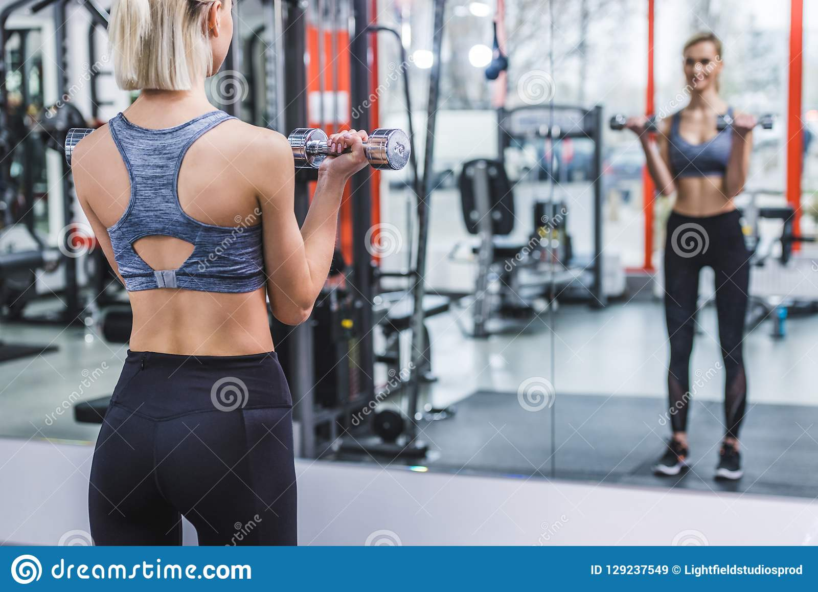 атлетическая молодая женщина разрабатывая с гантелями перед зеркалом