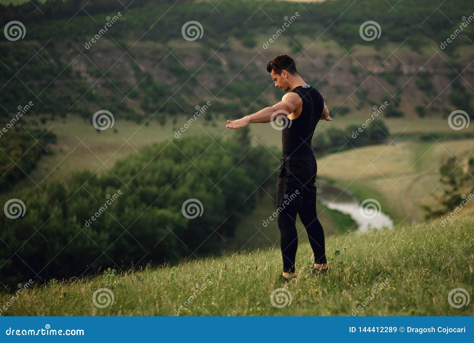 Атлетический молодой человек в sportswear делая тренировки с поднятыми руками и смотря вниз на предпосылке ландшафта природы
