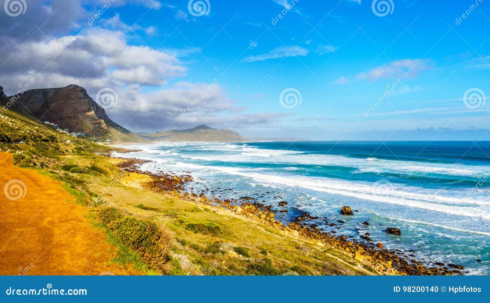 Download Атлантическое побережье вдоль дороги к пику ` S Чэпмена на маяке Slangkop Стоковое Фото - изображение насчитывающей пасмурно, облака: 98200140