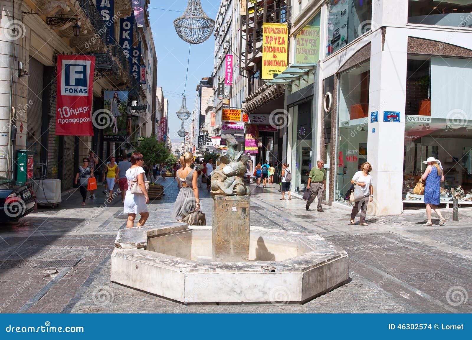 АФИН 22-ОЕ АВГУСТА: Ходящ по магазинам на улице Ermou с толпой людей 22-ого августа 2014 в Афинах, Греция