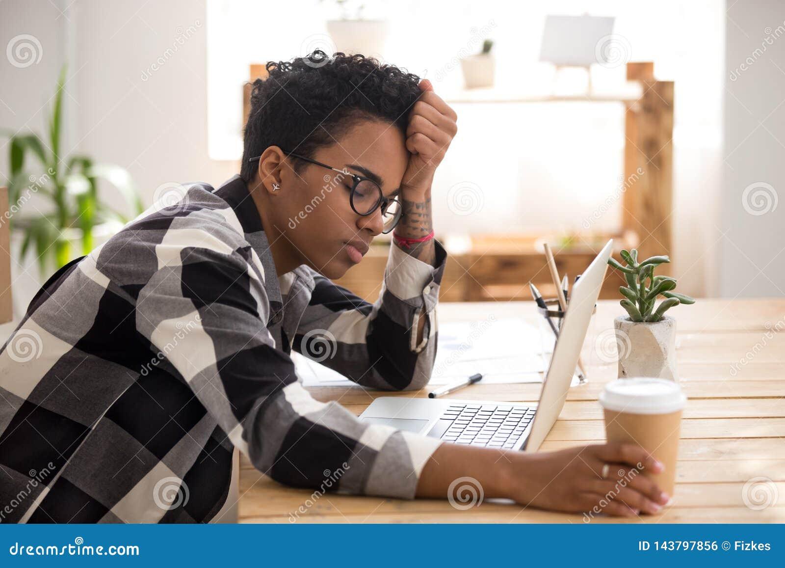Африканская женщина сидя на столе на офисе и спать