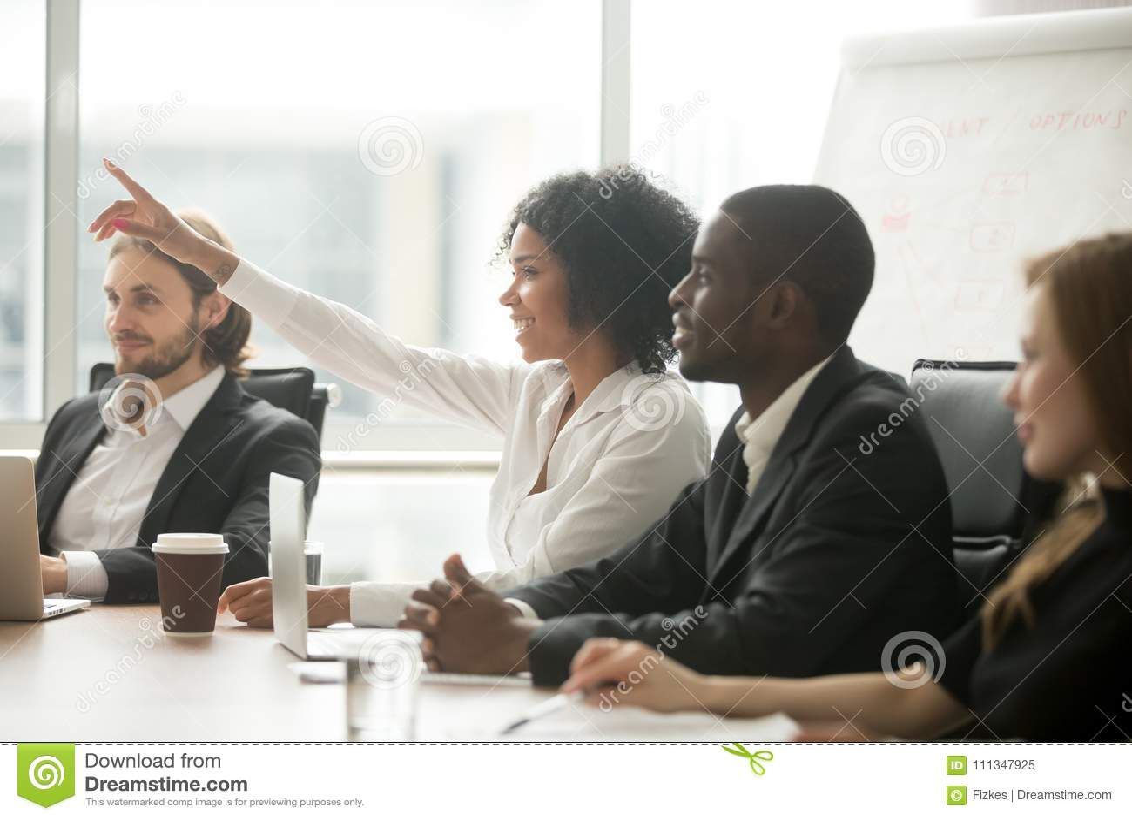 Африканская рука повышения женщины для того чтобы спросить вопрос на тренировке команды